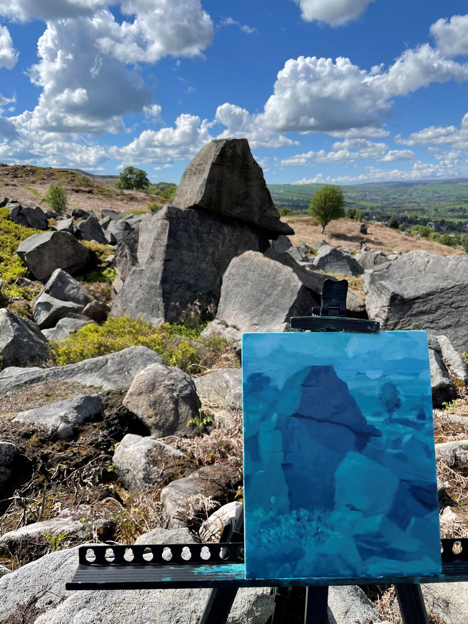 A painting on an easel before a rock on Ilkley Moor